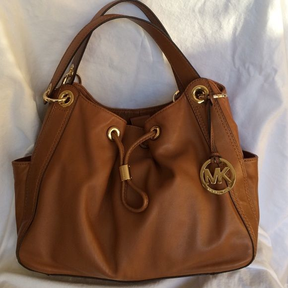 Authentic Michael Kors Leather Shoulder Bag This beautiful leather bag has had limited use and the leather still smells new. Inside has side pockets on both sides, including a zipper side pocket, as well as the center zippered pocket. This beautiful Michael Kors bag is a caramel color, which makes it perfect for summer and winter. Michael Kors Bags Shoulder Bags
