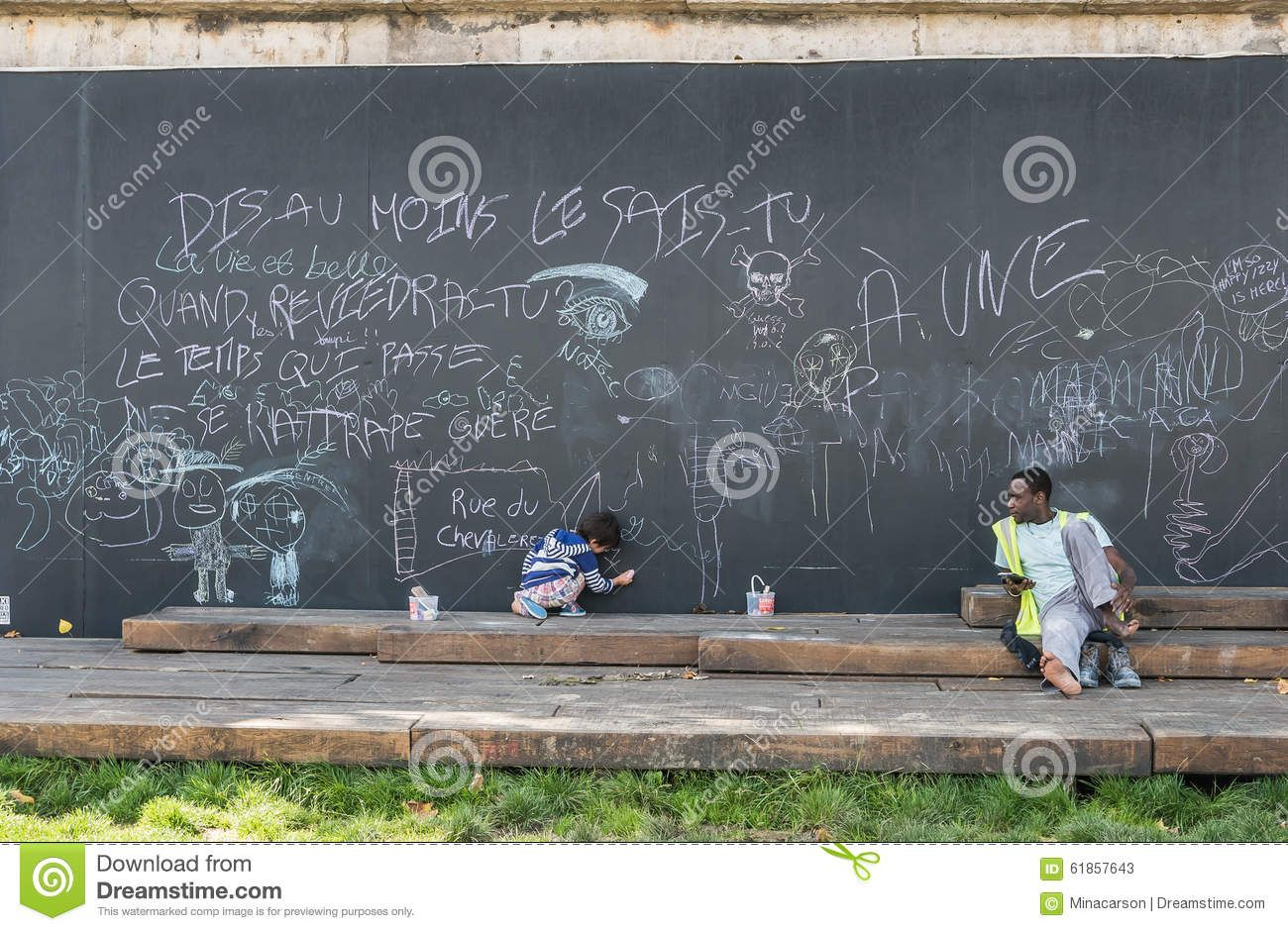 man watches child draw outdoor blackboard paris france sept berges