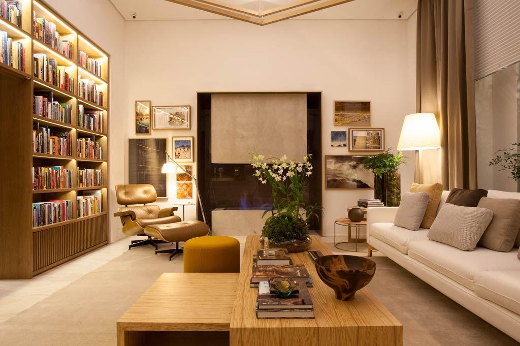 """28 salas incríveis de CASA COR SÃO PAULO para você se inspirar - Casa   """"A Biblioteca de Estar assinada pelo arquiteto e designer de interiores Bruno Gap ocupa 35 m². Tons terrosos, dos mais claros aos mais escuros, formam a paleta de cores dos revestimentos e móveis. A iluminação baixa e a lareira à álcool da Largrill contribuem para um clima aconchegante e intimista."""""""