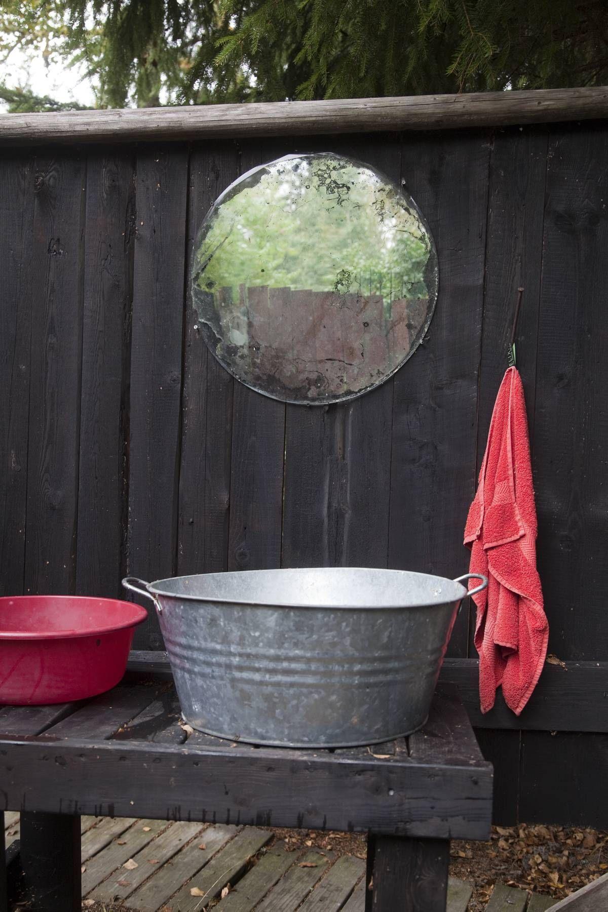 Pesupaikka on taivasalla. Kuuma vesi lämpenee vanhassa saunapadassa pesupaikan vieressä.