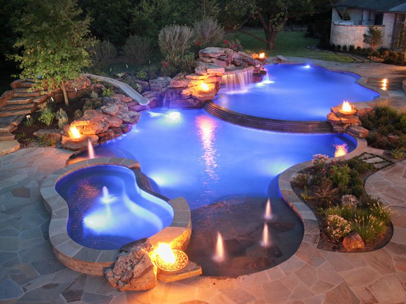 Swimming Pool Ideas white colonial home with grey patio and trees surrounding pool Natural Edge Pool With Spa Slide And Waterfall By Distinctive Pools
