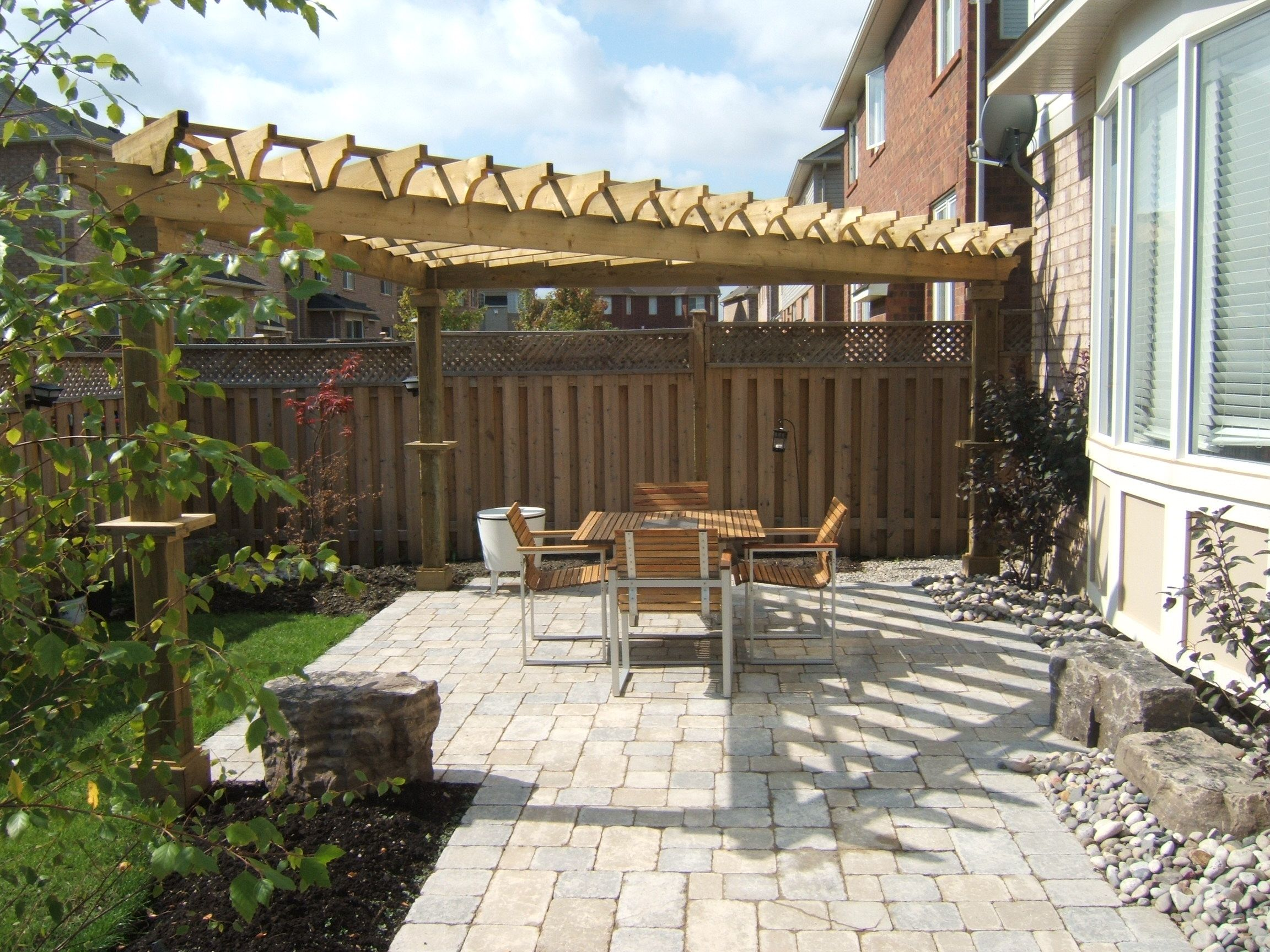 Triangular Pergola With Boots And Collars Over An Interlock Patio.