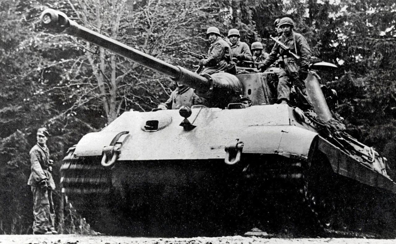 """German paratroopers riding on the armor of the tank Pz.Kpfw. VI Ausf. B """"Tiger II"""" (""""king tiger"""") during the offensive in the Ardennes. December 1944."""
