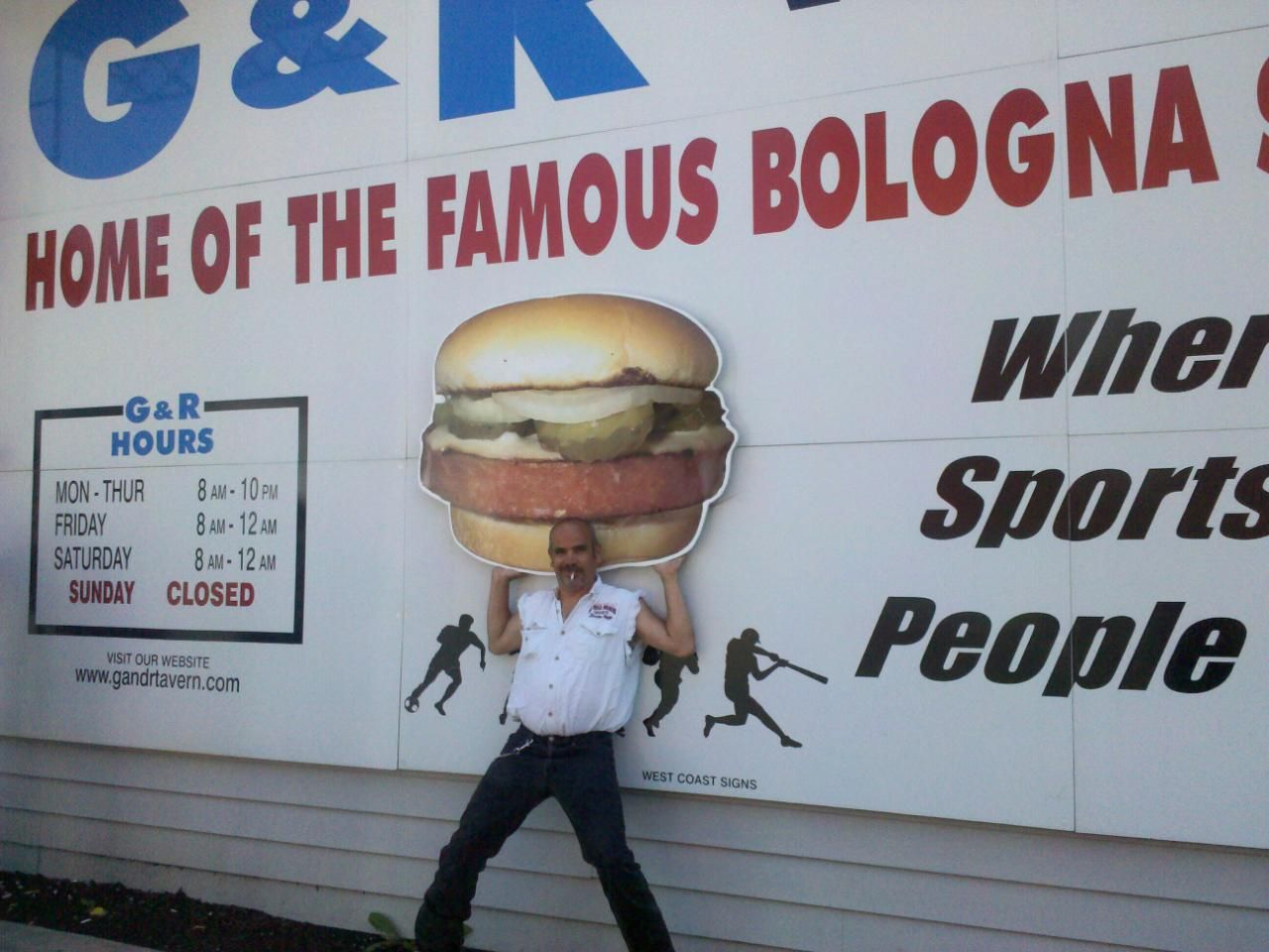 Some guy named Crude holding up the Bologna Sandwich pictured on the outside of the G & R Tavern. www.gandrtavern.com