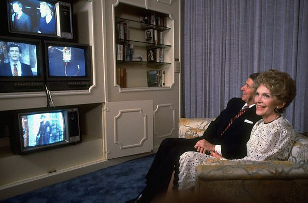 Nancy and Ron watch the returns on four televisions from a couch in a hotel suite in Los Angeles