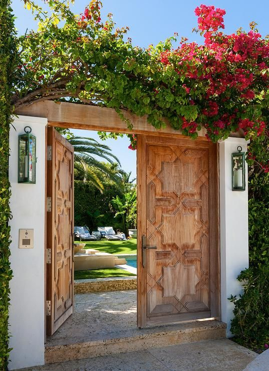 Weathered double doors lit by outdoor wall lanterns open to the lush