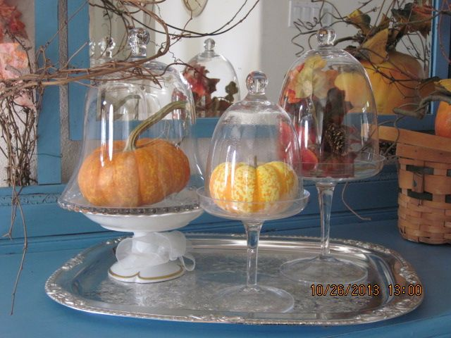 A view from my entry way.  Three cloches on a silver tray, with adorable small pumpkins and leaves for accents.  Add a grapevine swirling around and you have a simple, lovely effect.