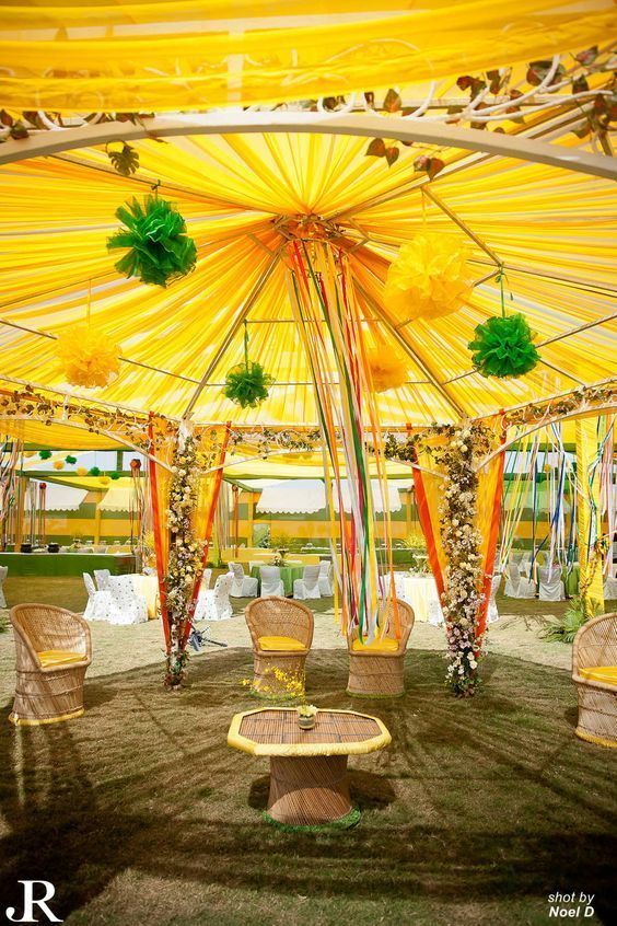 love this decor in yellow tent with yellow canopy hanging ribbons bamboo chairs outdoor mehendi decor indian wedding decor ideas floral