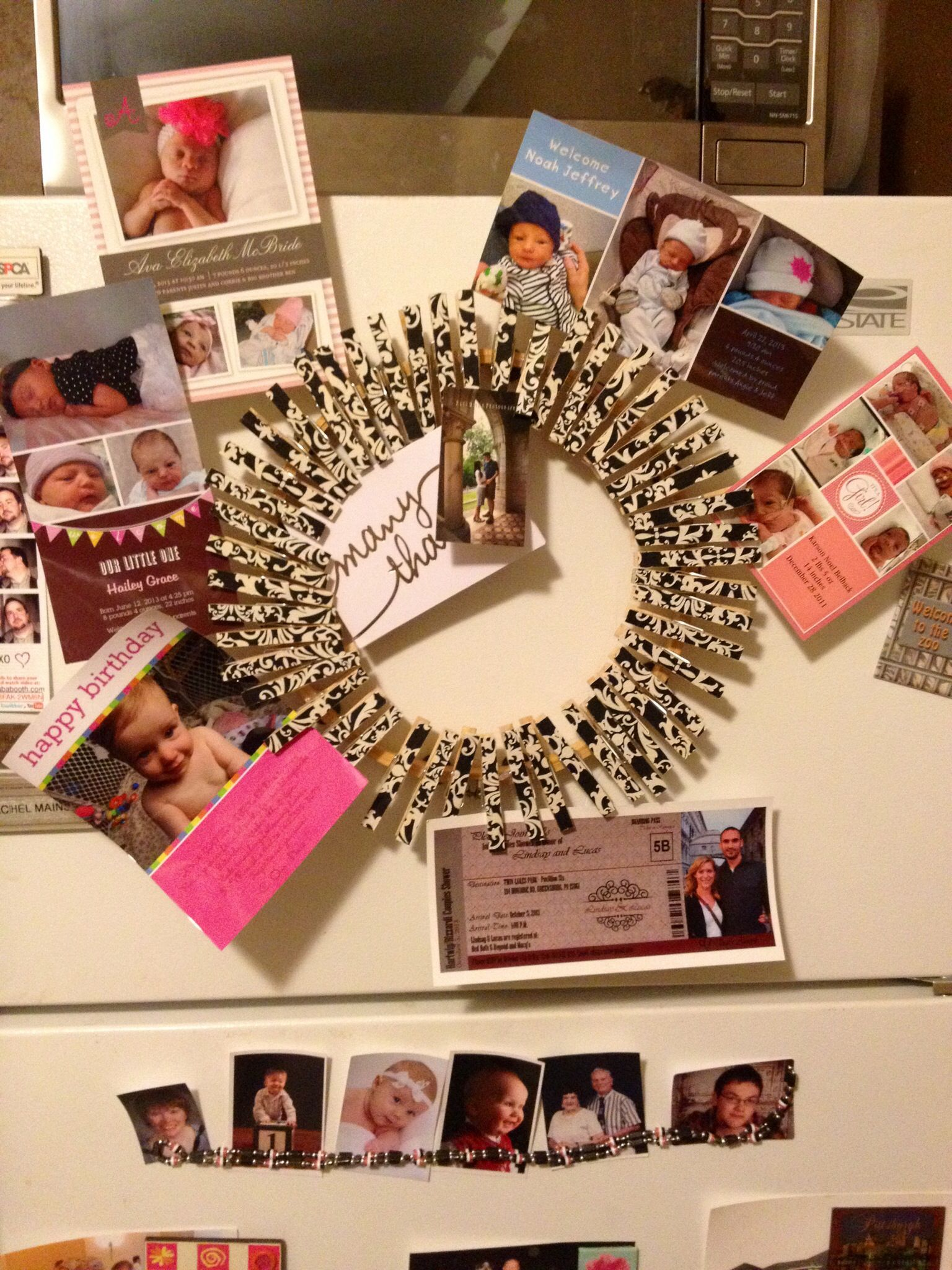 Mod podged wrapping paper to clothes pins then  hot glued to wreath. Added magnets for organization of the fridge. All of those cute baby announcements.