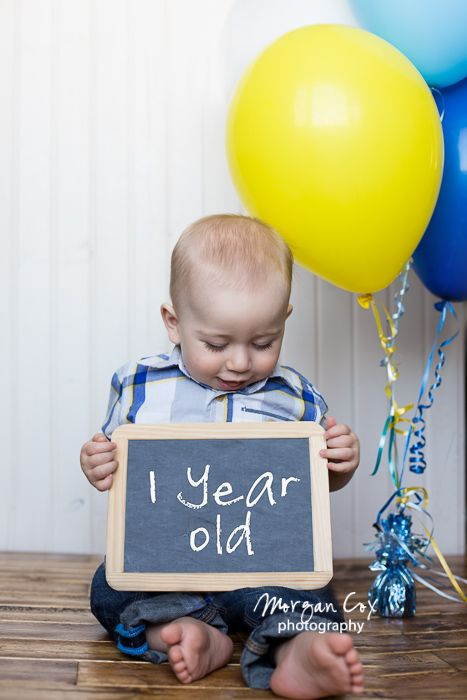 one year old boy holding chalk board for first birthday photos