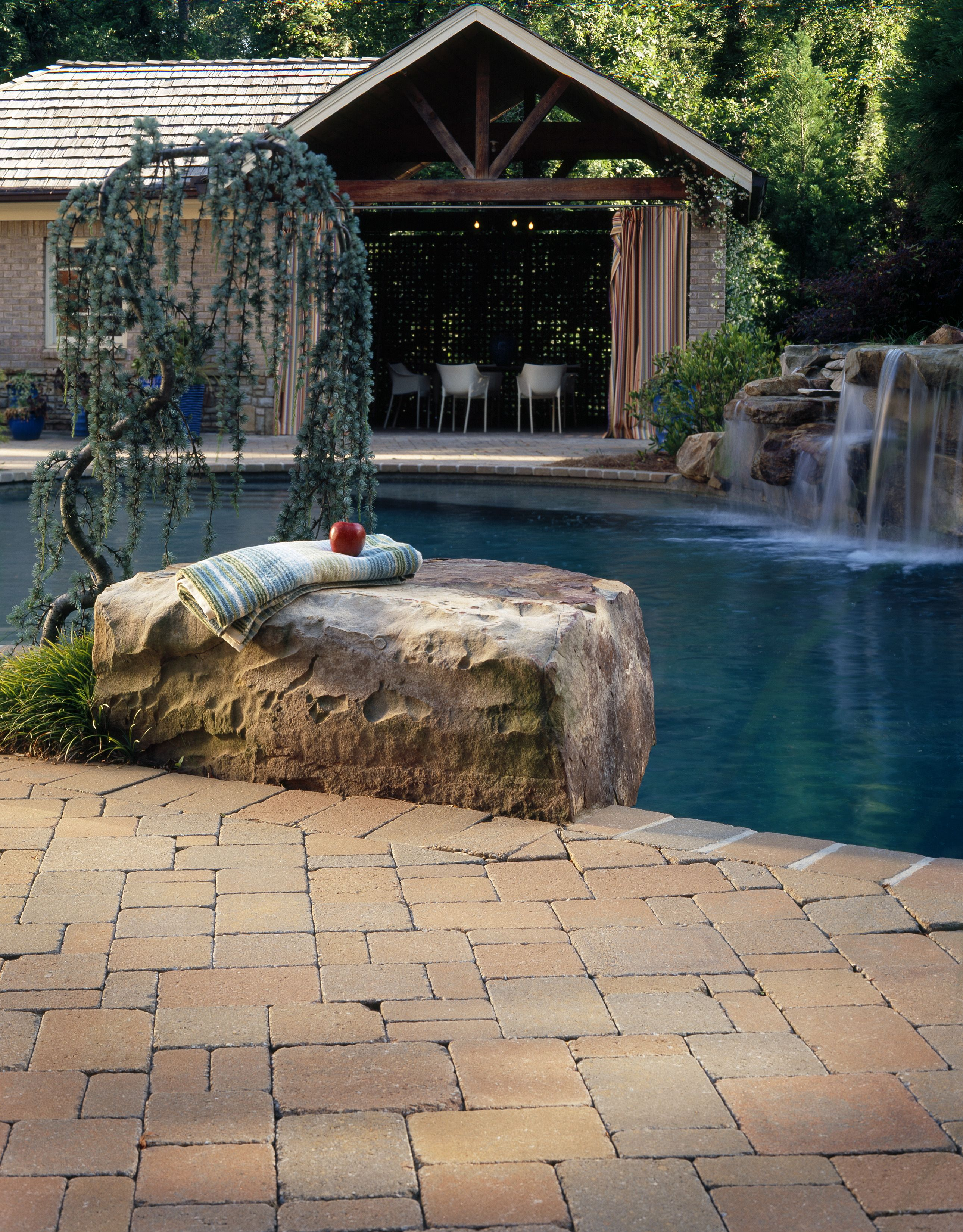 outdoor living. red / brown paver pool deck with natural stone