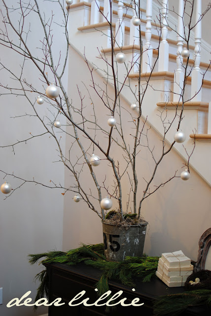Twig Tree for centerpiece on table but instead of silver ornaments, we hang little ghosts made out of tissues.