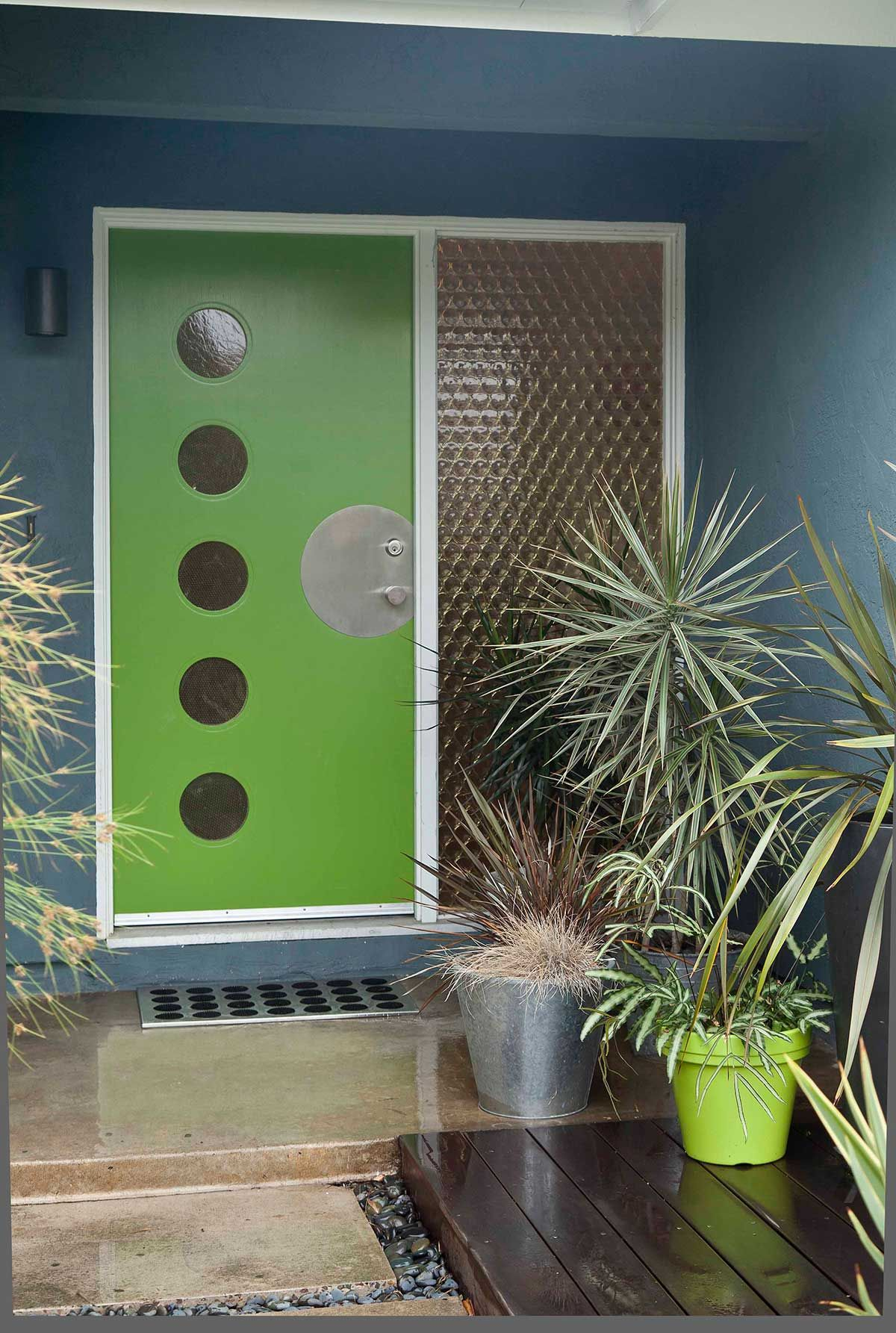 the green door and potted plants make this mid century