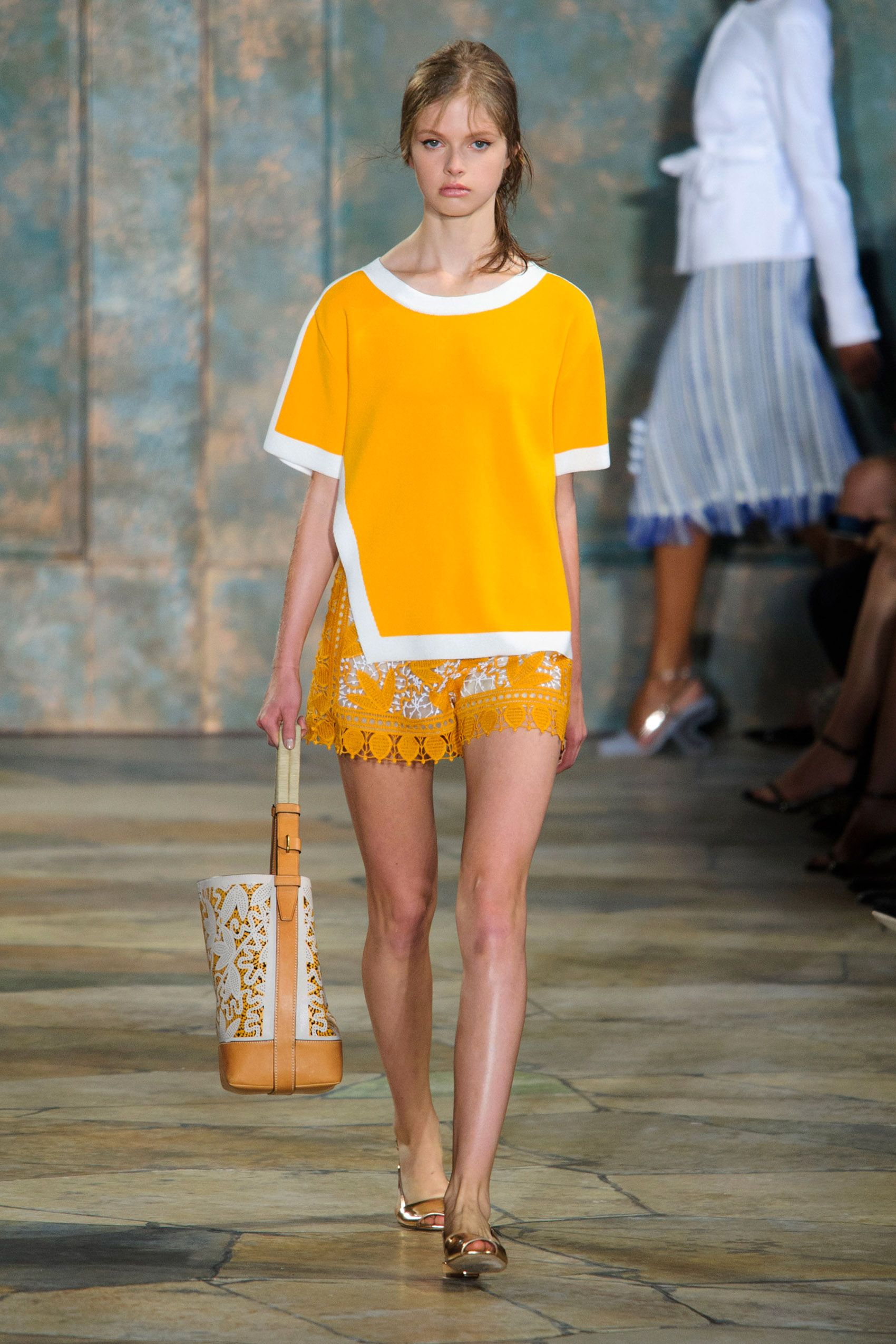 There were hints of that Moroccan vibe in a bright yellow cotton smock sweater with pom poms, paired with lace shorts.   - HarpersBAZAAR.com