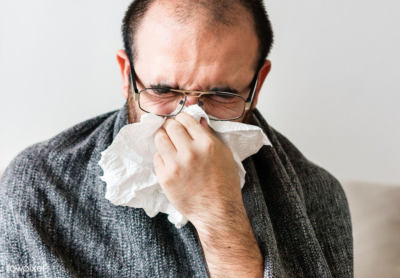 Download premium photo of Man sneezing into tissue paper