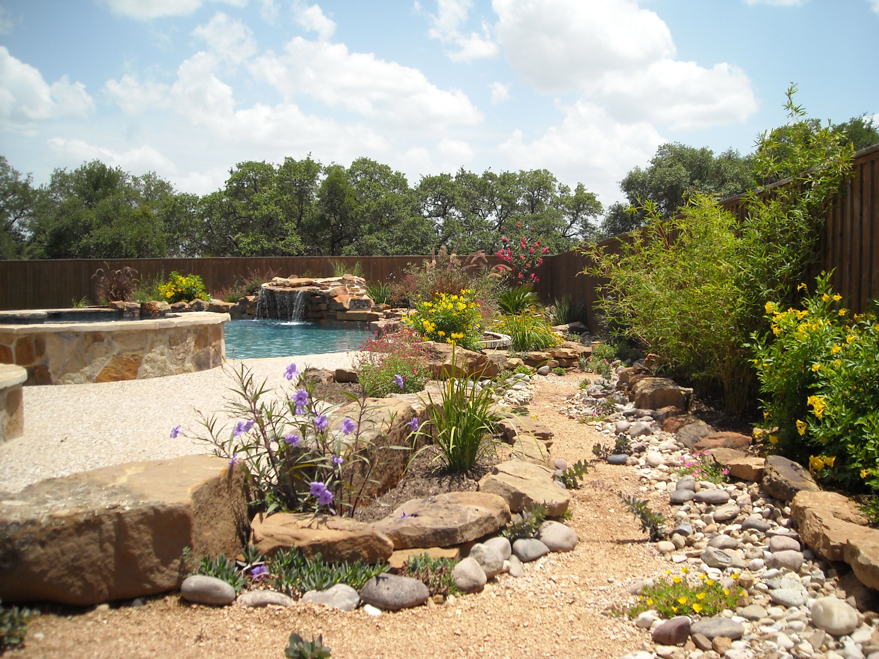 Mediterranean style outdoor cushion rock patio umbrella hot tub patio - Native Landscaping Around A Pool With Hot Tub And Outdoor Kitchen It Even Has A