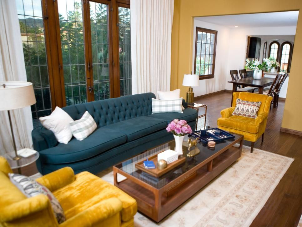 Gold Velvety Chairs And A Deep Teal Tufted Sofa Complement The Rich Ochre  Colored Walls In