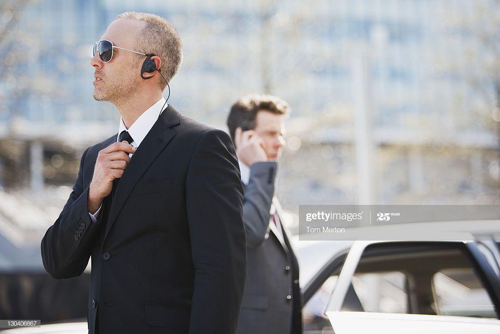 Bodyguard talking into earpiece bodyguard business