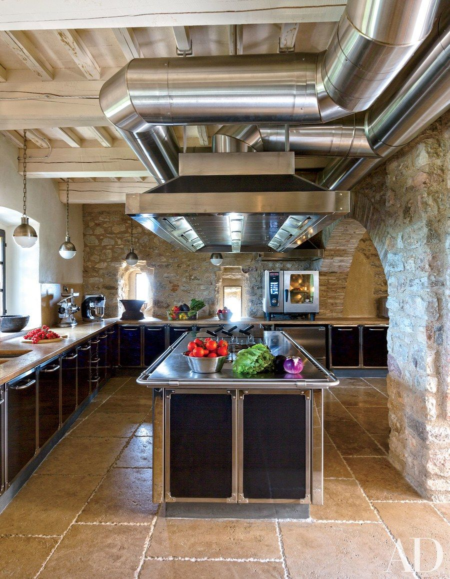 Architect Domenico Minchilli and decorator Martyn Lawrence Bullard reimagined a crumbling medieval castle on a prime spot in Italy's Umbria region. In the kitchen, lacquer cabinetry is juxtaposed with dramatic ceiling vents and exposed brick.