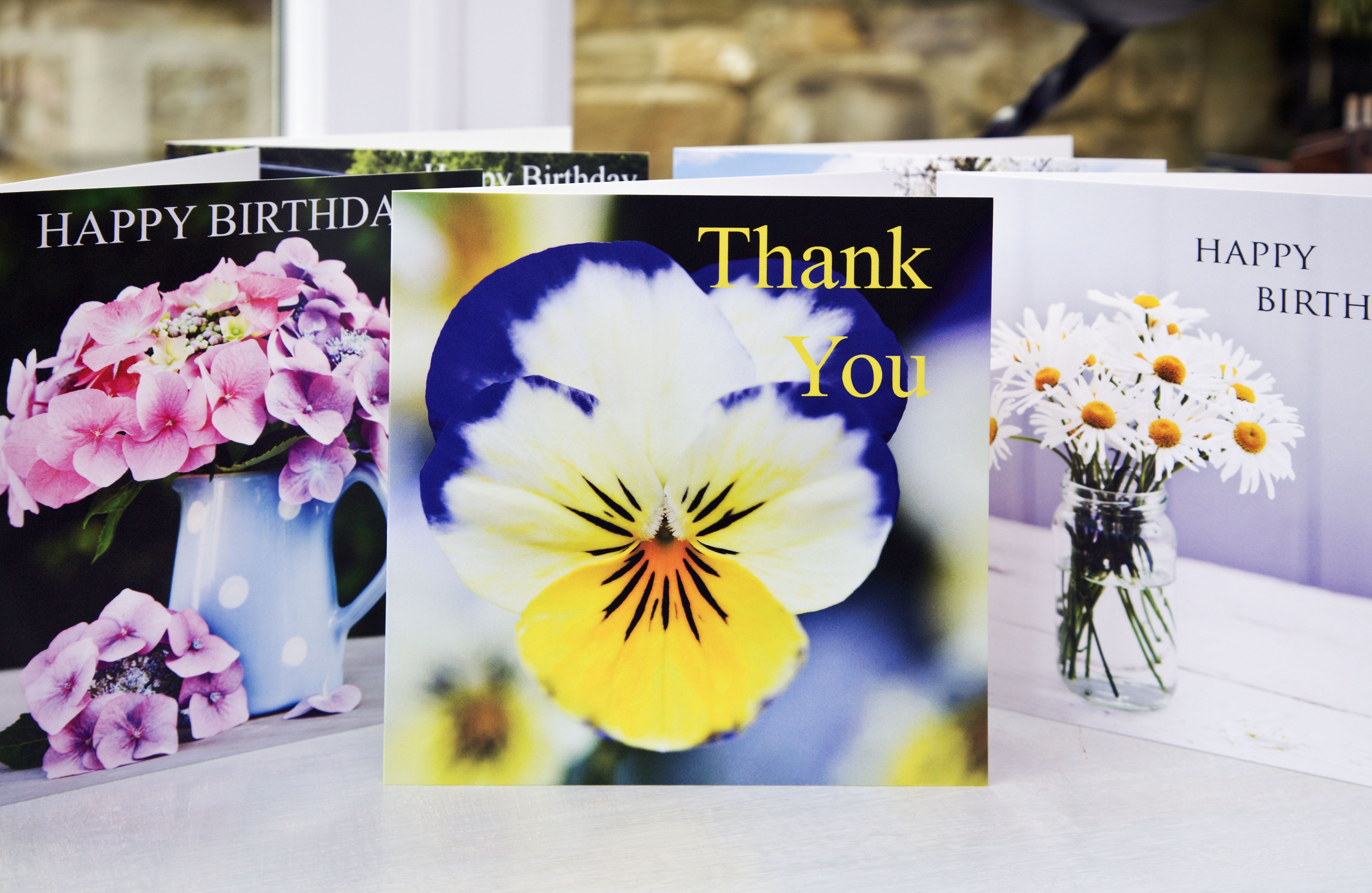 JNC016    Greetings card.  15cm x 15cm  'Thank You' Viola flower, blank on the inside for your own message, cello wrapped and comes with a white recycled envelope.  Designed and printed in the United Kingdom.
