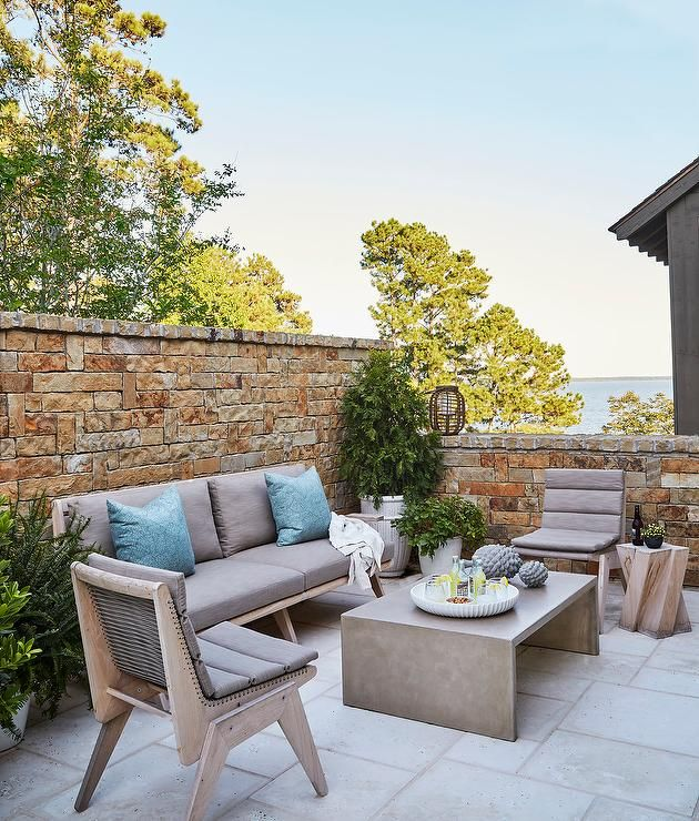 Gorgeous Patio Is Filled With A Gray Teak Sofa And Chairs Adorned With Blue Outdoor Pillows Facing A Gray Conc Outdoor Sofa Teak Outdoor Outdoor Furniture Sets