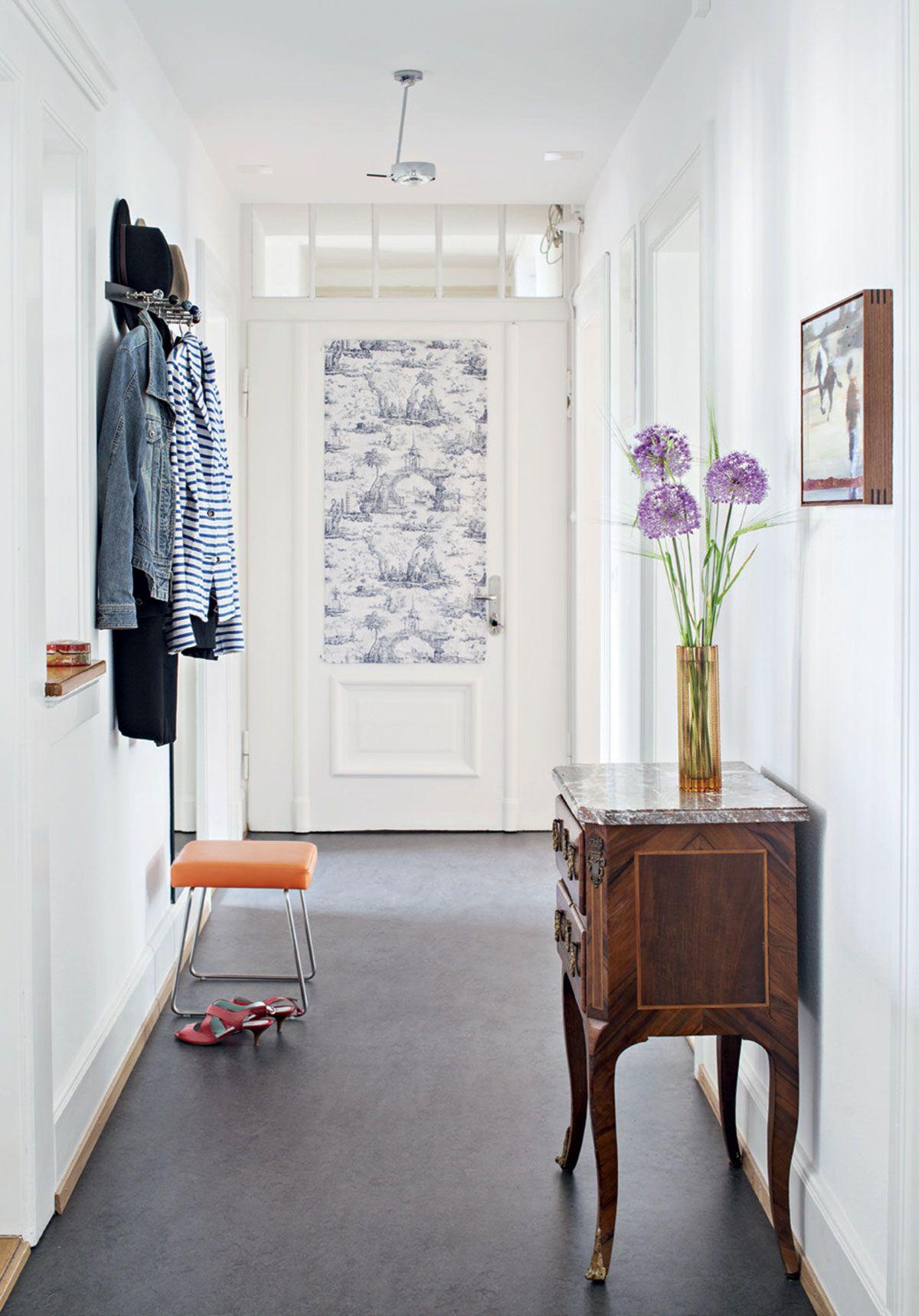 Doris on vaihtanut eteisen mustan lattian tumman-harmaaksi, joka sopii tilaan hyvin. Näkymä kylpyhuoneen ovelta kohti rappukäytävään johtavaa ulko-ovea on rauhallinen. Oranssi jakkara on särmikäs pari antiikkilipastolle, joka on Doriksen ex-anopilta. Seinälle on ripustettu australialaisen taiteilijan, Brett Weirin öljyväriteos.