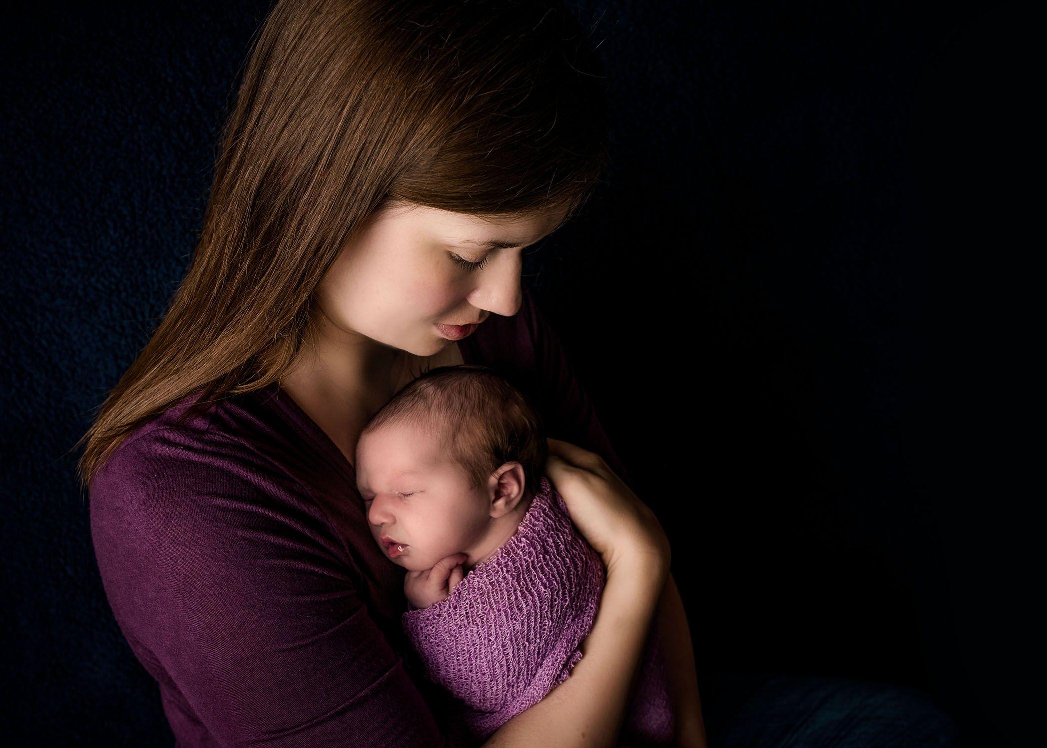 Mom holding newborn baby girl on her chest one big happy photo