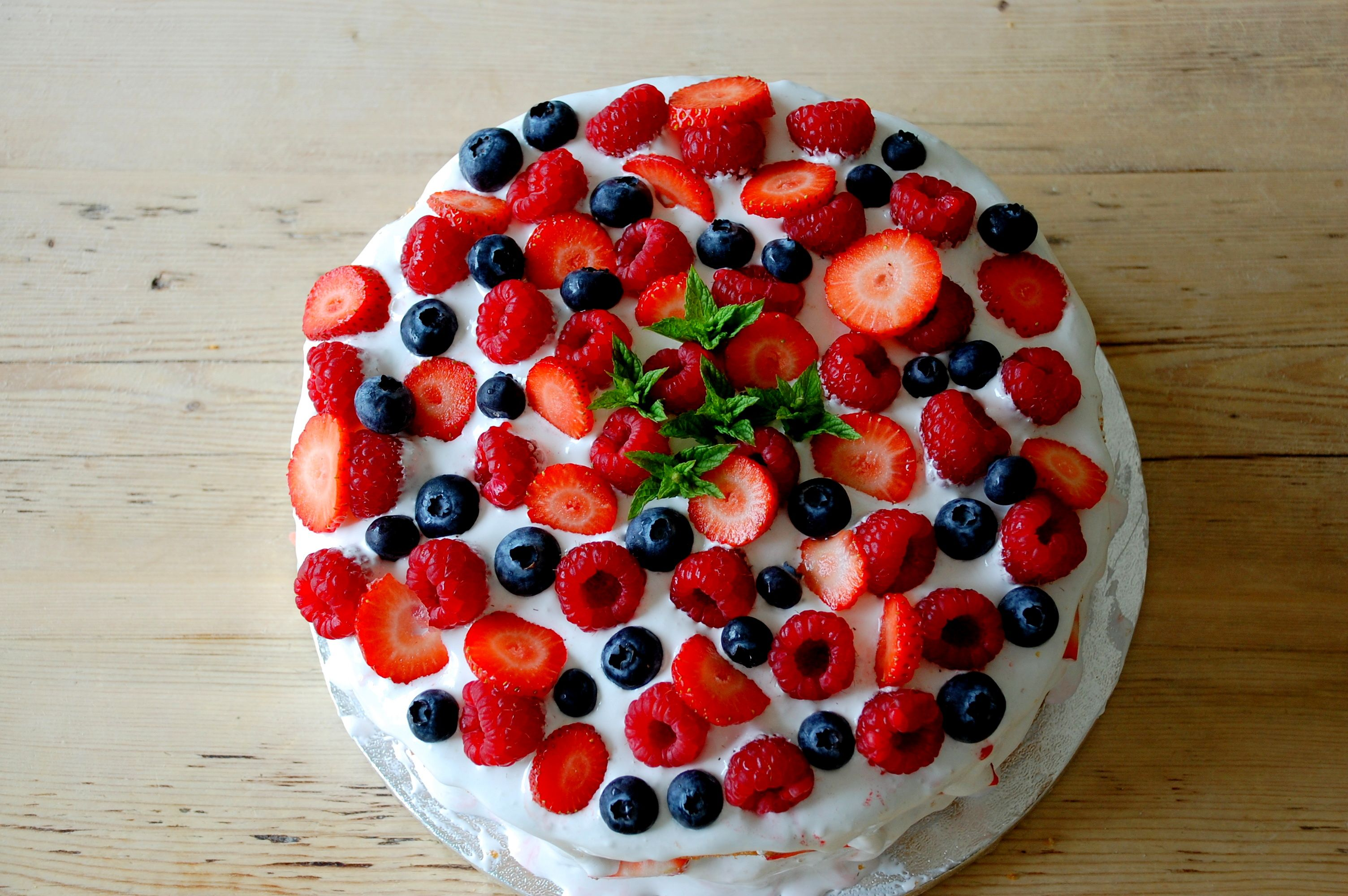 Marshmallow layered birthday cake with fresh fruit and mint