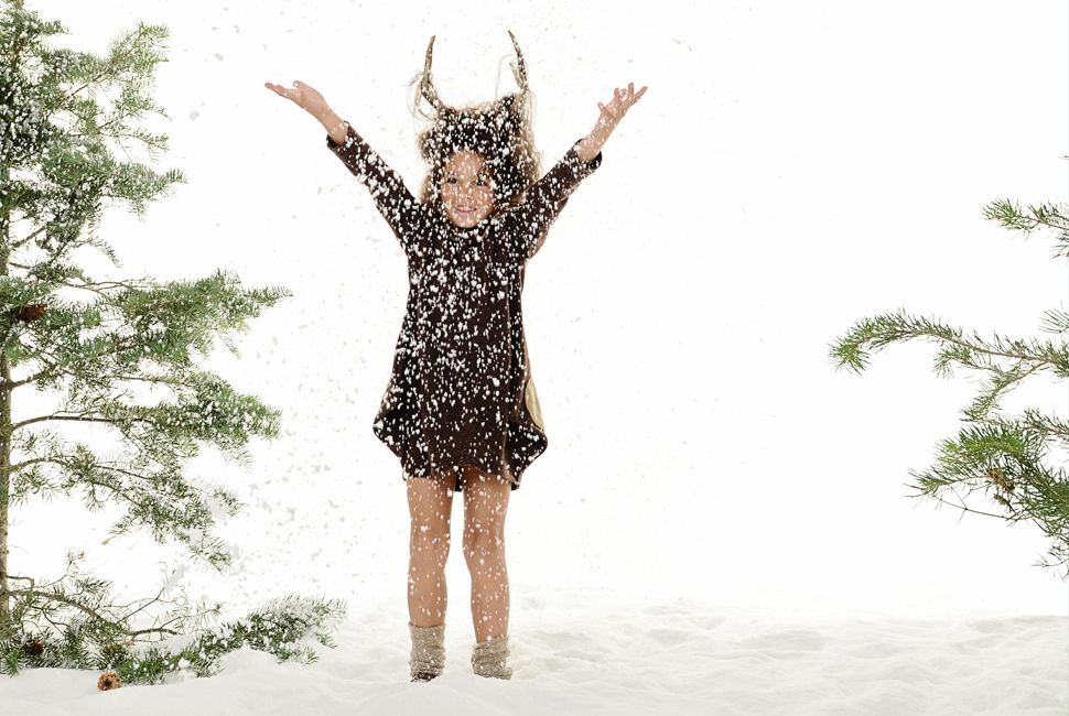 www.frostedproductions.com l #utah #photographer #editorial #photography #little #girl #throwing #snow #in #the #air #brown #dress #cute #clothes #for #little #girls #studio #pine #trees #antlers #amazing #hair
