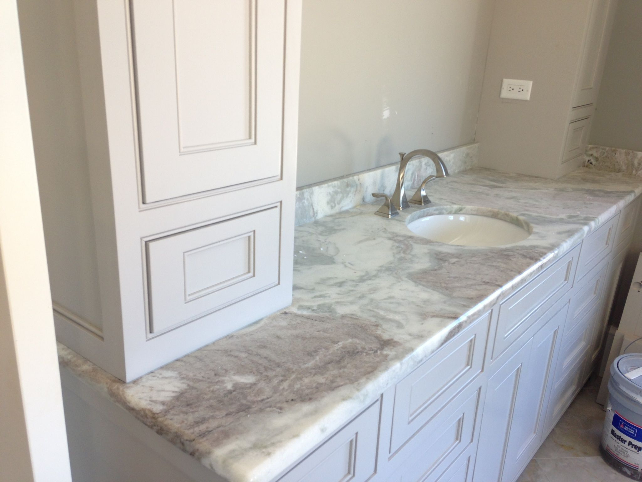 This Ocean White quartzite countertop provides the elegant look of marble  in this bathroom, yet