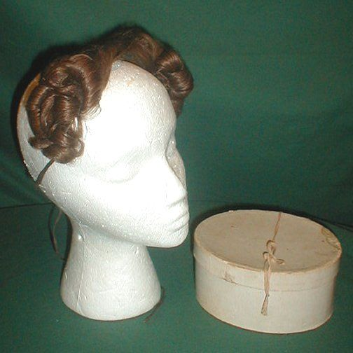 A unique 1830's false front hair piece that comes in its original box.  The hairpiece war worn by Mrs. Warren Birds.   Her name and information on how she wore it is written on the bottom of the box.  According to the note the piece was worn with a day cap and a large bonnet of the time period.   The light brown hair has an auburn tinge. It is attached to netting and has a tie back closure.