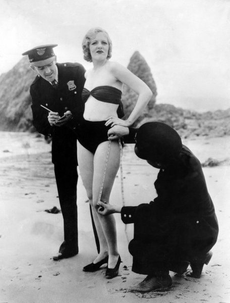 Policemen measuring Peggy Graves's swimming costume, to check whether it meets minimum clothing requirements, 1933 (via Retronaut)