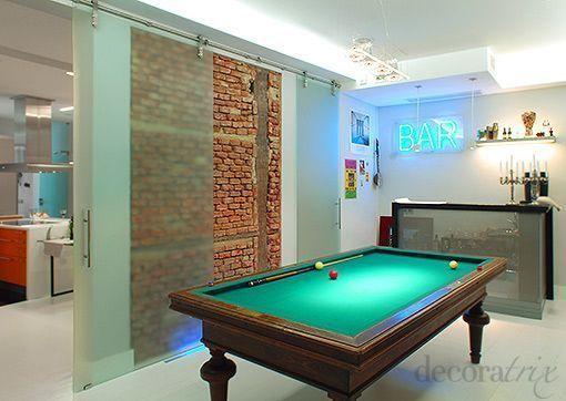 Una sala de juegos con billar dentro de casa