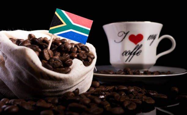 south african flag in a bag with coffee beans isolated on black