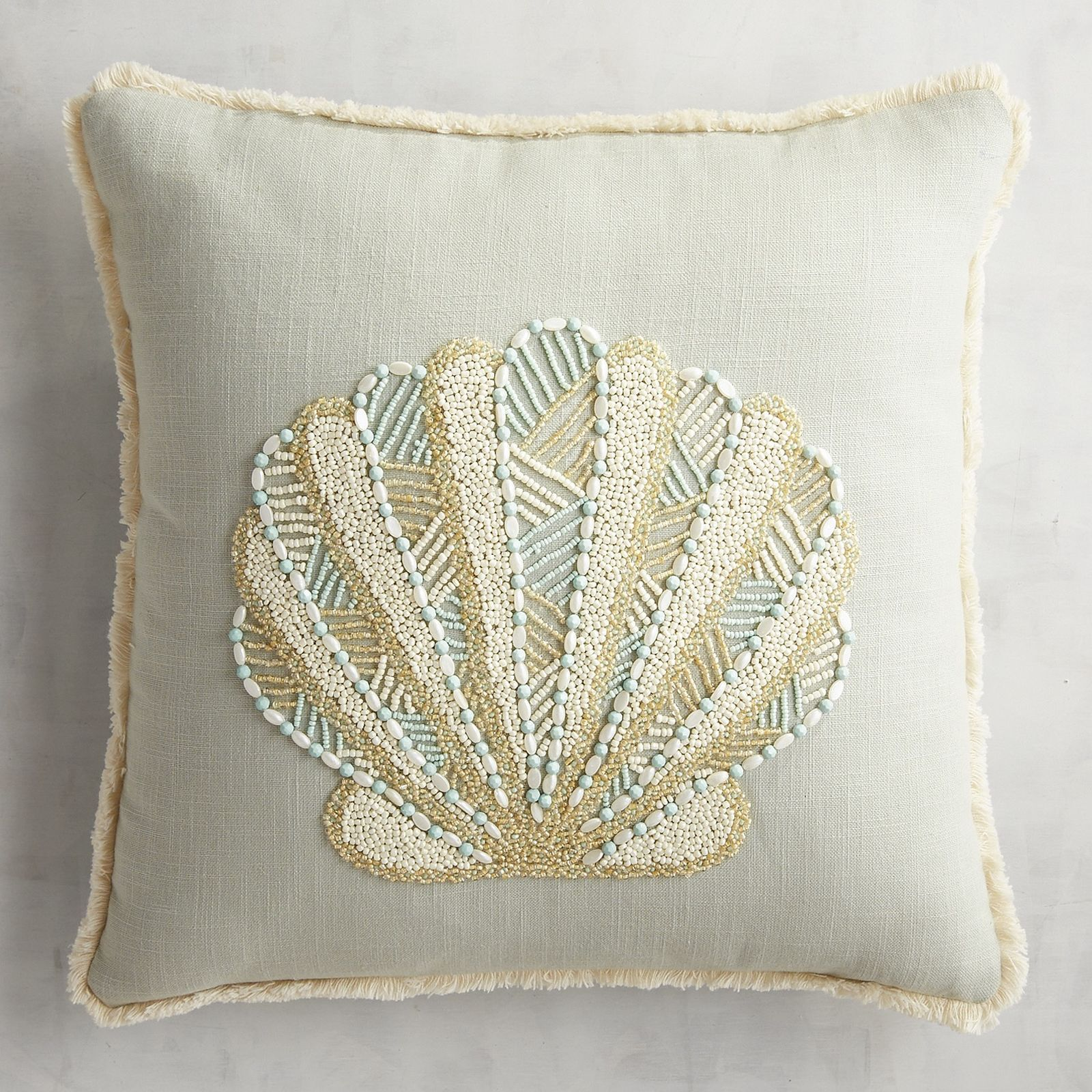 Seeking safe harbor on your sofa, our fan shell fashioned of sparkly beadwork in a calming sea-and-sand color palette rides the wave of sophisticated coastal chic.