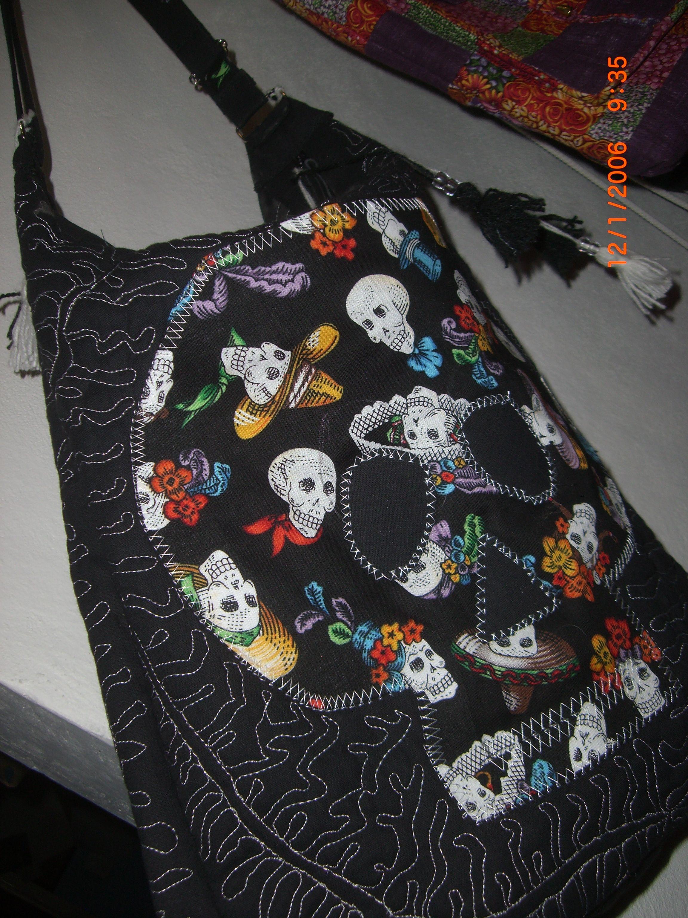 negra con aplicación de calavera, bolsillos interiores y un asa en los extremos, se cierra con cremallera