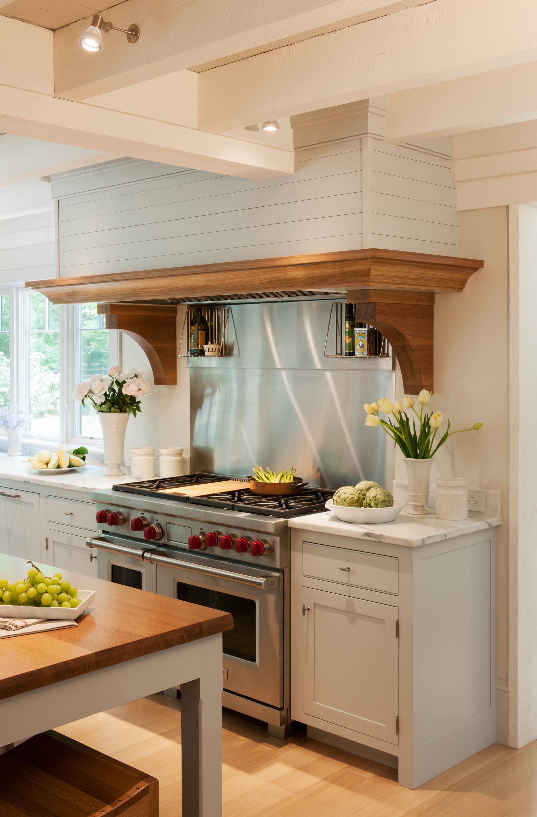 This custom Crown Point Cabinetry range hood is designed ...