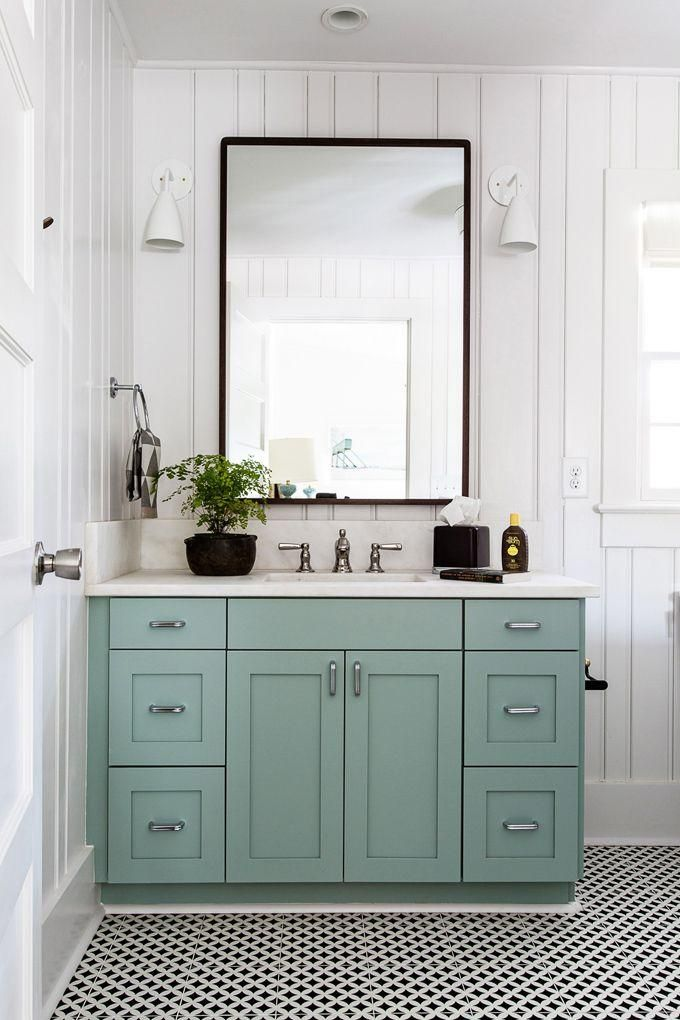 Love this minty green cabinet under the marble sink, with black framed mirror, white sconces, and black and white patterned floor tiles in this adorable bathroom.