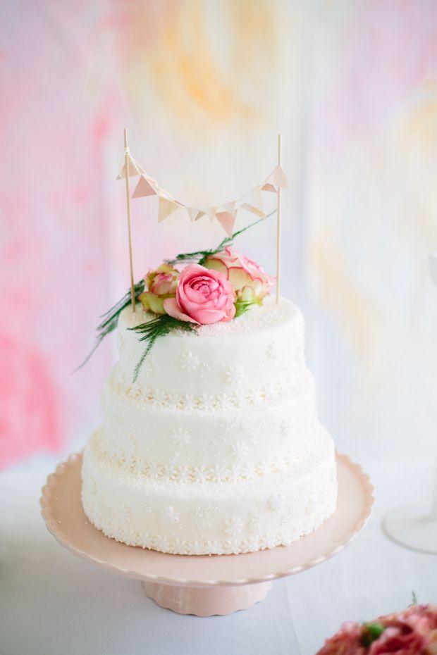 Girlande und frische Blumen auf Hochzeitstorte