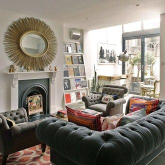 Book Display A Statement Mirror Bold Cushions And Feature Wall Of Books Artfully Facing Living Room