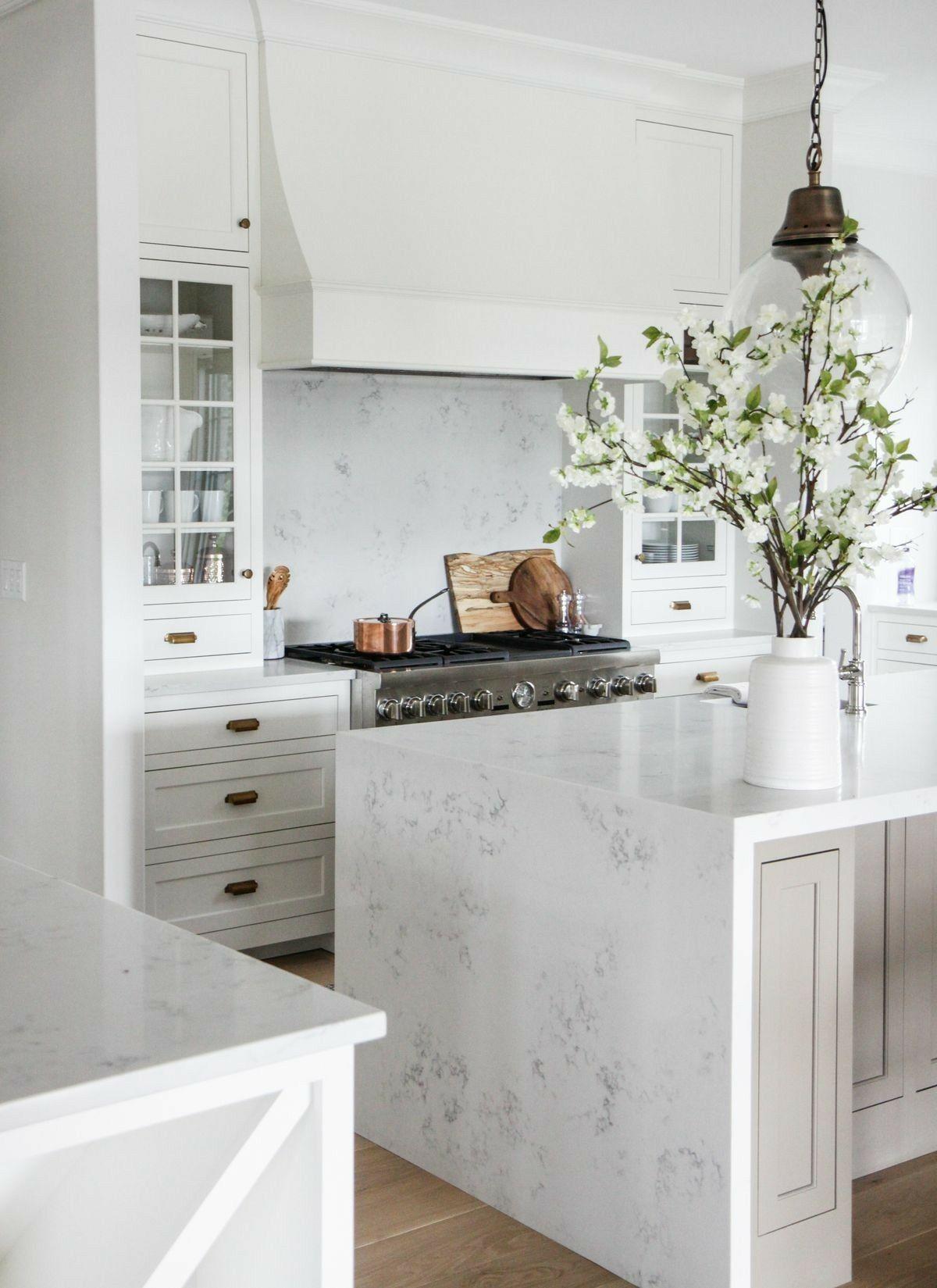 White Kitchen With Natural Accents Marble Waterfall Island And Pretty White Branches Clean Crisp Interior Design Kitchen Kitchen Interior Home Decor Kitchen