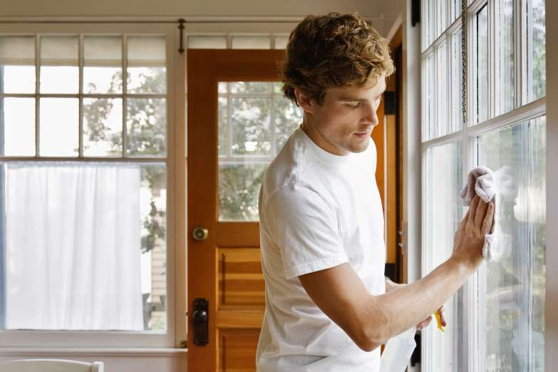 Man cleaning house windows gravity imagestaxigetty