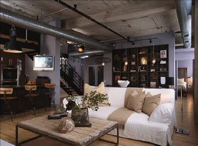 Manages to look warm and inviting, despite the concrete ceiling and exposed ducts and pipes. Love it.