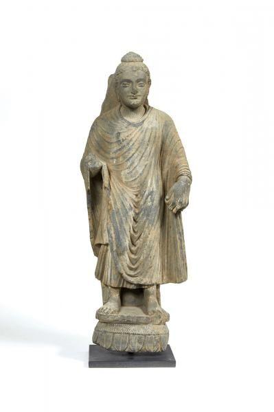 GANDHARA - Art gréco-bouddhique, IIe/IVe siècle Bouddha en schiste gris, se tenant debout sur un socle lotiforme, sa robe retombant en plis harmonieux, ses cheveux ondulés ramassés en un chignon, son front portant l'urna. (Eclats et manques.) H.76,5 cm.