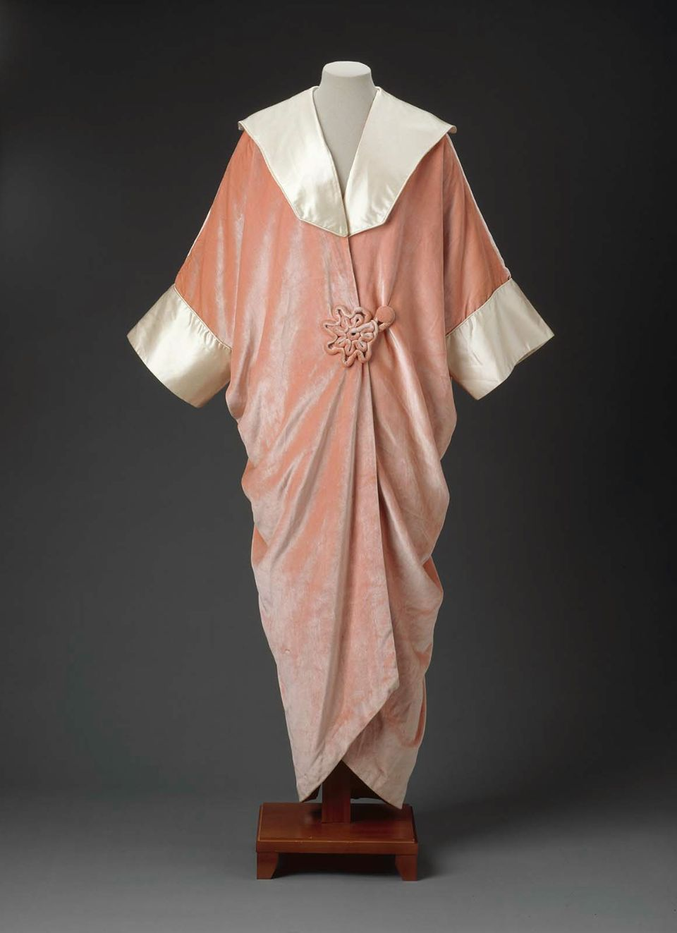 Evening coat. Jean-Philippe Worth, 1910–20. Coral pink velvet with satin collar and cuffs, coral pink silk satin lining. Loose kimono shape gathered in back and secured with pink corded velvet rosette; rosette also at front opening.