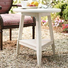 """Weathered end table with a tripod silhouette.Product: End tableConstruction Material: WoodColor: LinenFeatures:Part of the Paula Deen Home Collection Distressed finish Tripod designDimensions: 26"""" H x 24"""" DiameterNote: Chair not included"""