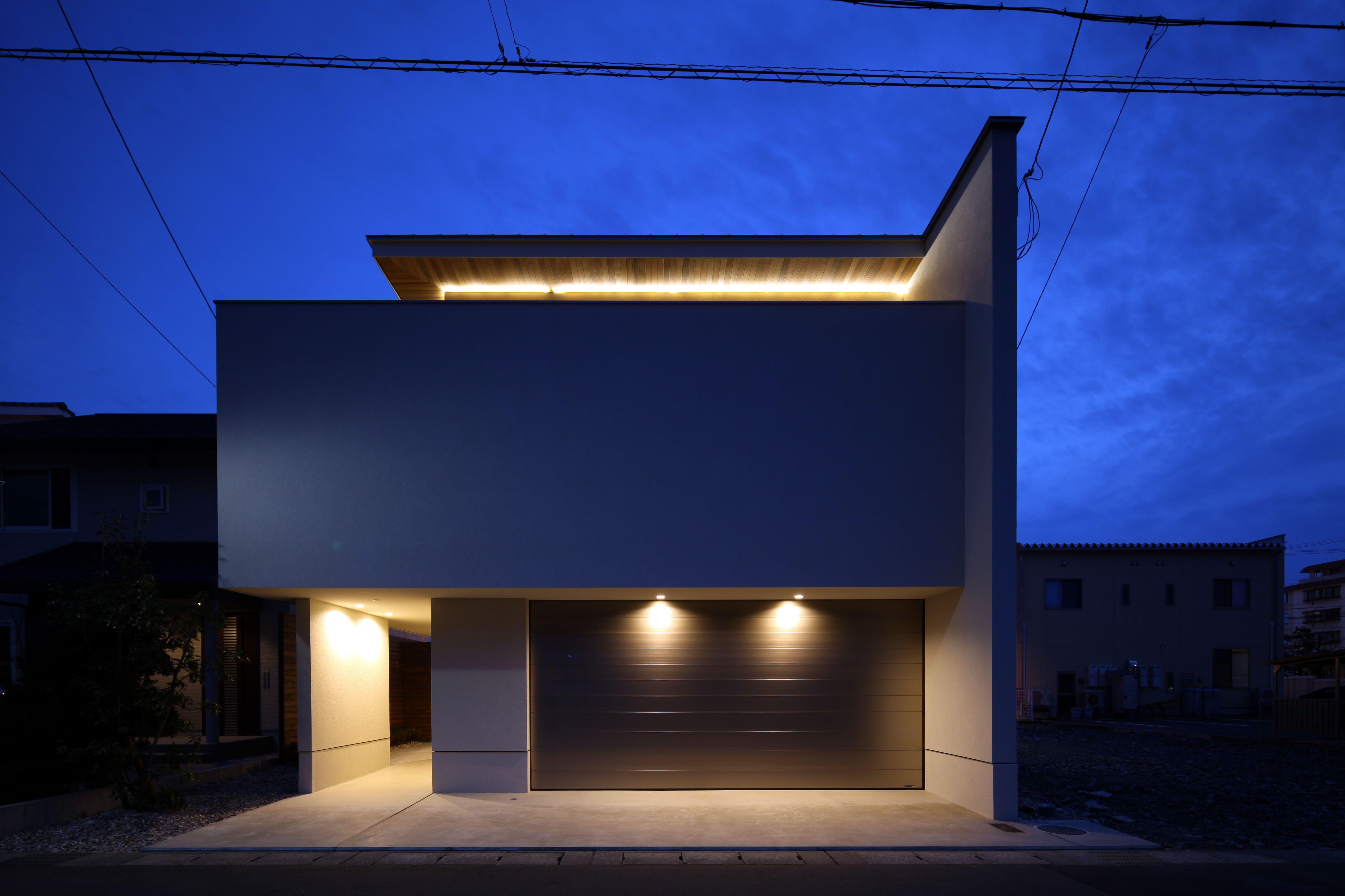 印象的な品のある照明計画としました 照明 スポットライト ファサード 外観 シャッター 玄関アプローチ 屋根 軒天 夕景 シンプル モダン Lighting Spotlight Facade Shutter Sophisticat 小さな家の外観 現代建築の住宅 モダンハウスの外観