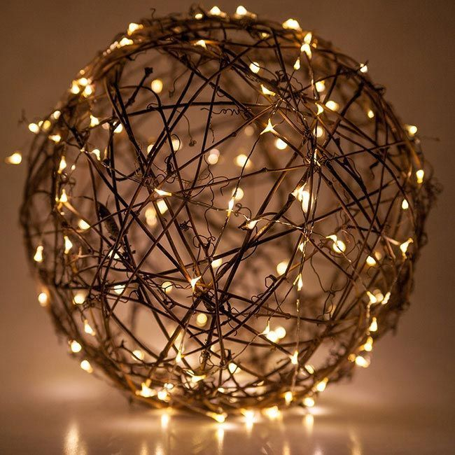 Wrap grapevine balls with fairy lights, then hang from tree branches