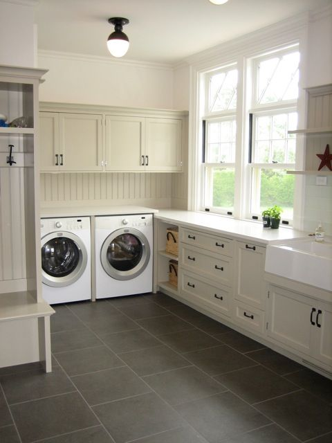 Contemporary Laundry Room Features Beige Cabinets Topped With