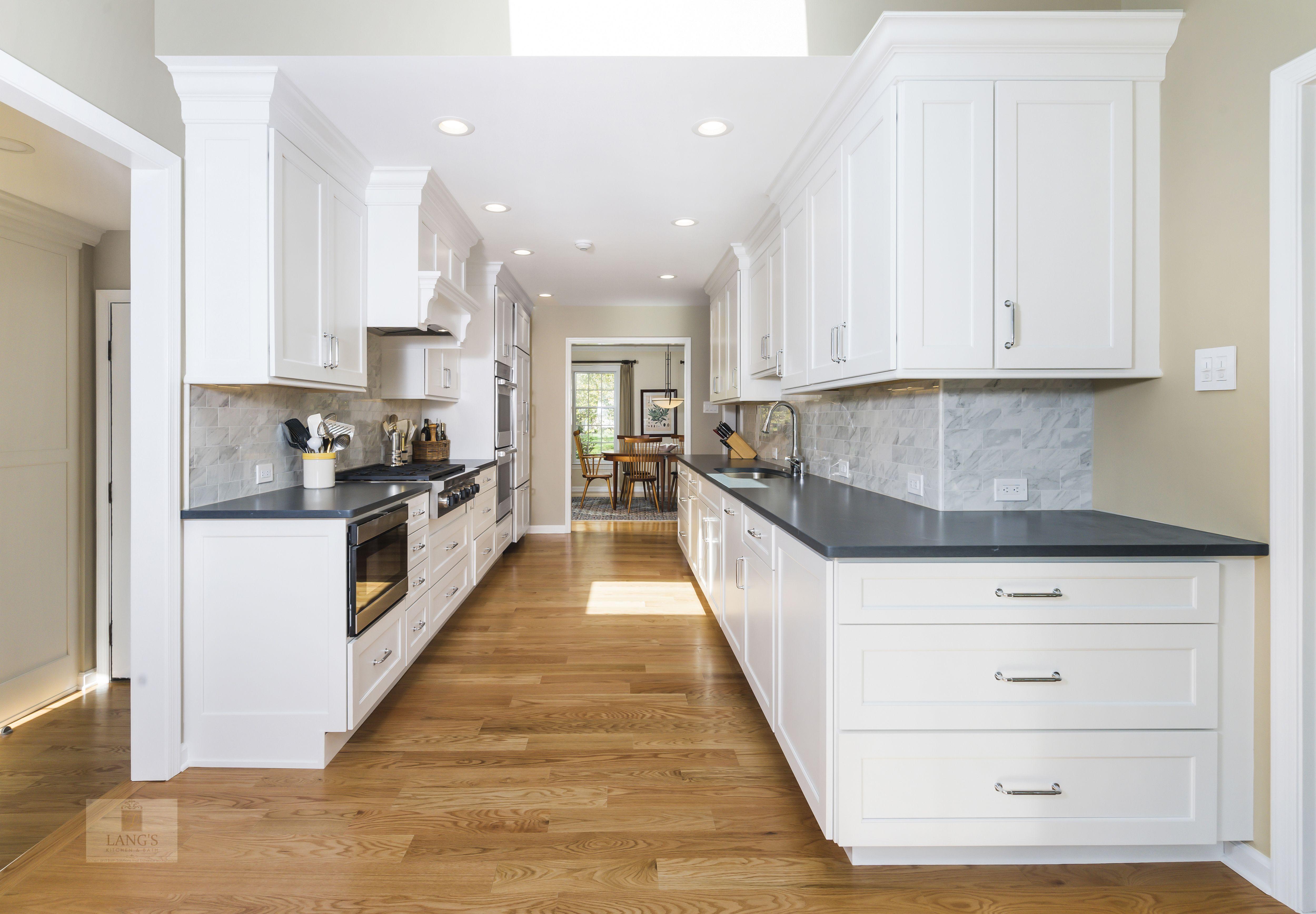 This Galley Style Kitchen Design Is A Bright Space Featuring Dura Supreme White Kitchen Cabinets Cont Galley Kitchen Design Galley Style Kitchen Kitchen Design